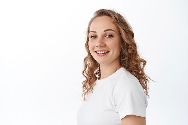 Retrato de uma mulher loira atraente com cabelo encaracolado, vire a cabeça para a frente e sorria feliz, parecendo despreocupada, em pé sobre uma parede branca