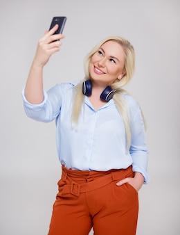 Retrato de uma mulher loira bonita e feliz, ouvindo música e tirando uma foto de selfie com telefone inteligente sobre fundo cinza