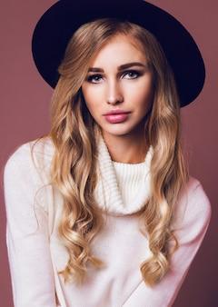Retrato de uma mulher loira bonita posando de chapéu