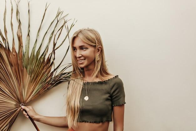 Retrato de uma mulher loira bronzeada de cabelos compridos em uma camiseta verde escuro, sorrindo sinceramente e segurando uma folha de palmeira seca no fundo branco
