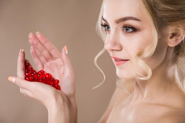 Retrato de uma mulher loira com cápsulas vermelhas de vitaminas nas mãos dela