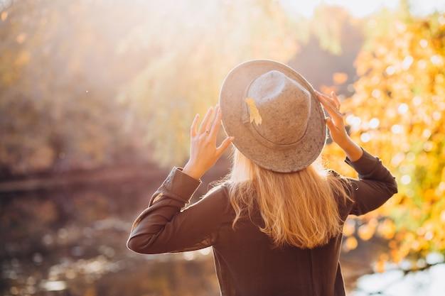 Retrato de uma mulher loira com chapéu cinza na floresta de outono