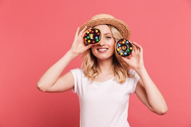 Retrato de uma mulher loira com chapéu de palha rindo enquanto segura rosquinhas doces saborosas isoladas sobre uma parede rosa