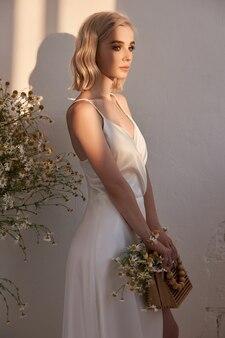 Retrato de uma mulher loira com um vestido de noiva branco ao sol da tarde
