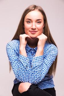 Retrato de uma mulher loira confiante com a mão no queixo, sentada à mesa contra uma parede branca