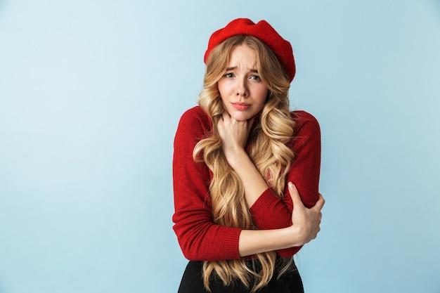 Retrato de uma mulher loira de 20 anos, assustada, usando uma boina vermelha, sentindo-se confusa em pé, isolada