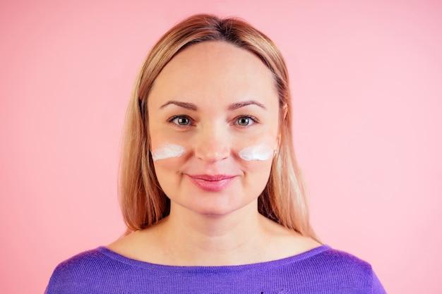 Retrato de uma mulher loira de 30 a 35 anos com hidratante no rosto em um fundo rosa no estúdio