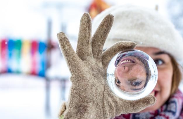 Retrato de uma mulher loira de boina, jaqueta e cachecol, segurando na mão uma bola de cristal em um parque nevado.
