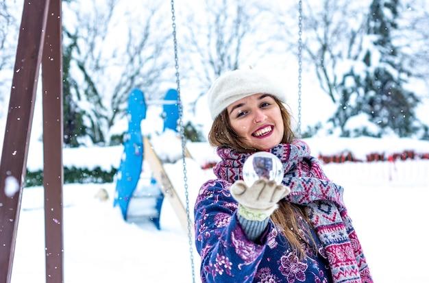 Retrato de uma mulher loira de boina, jaqueta e lenço, segurando uma bola de cristal em um parque nevado.