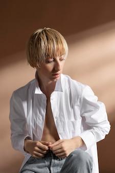 Retrato de uma mulher loira de cabelos curtos posando com uma camisa branca