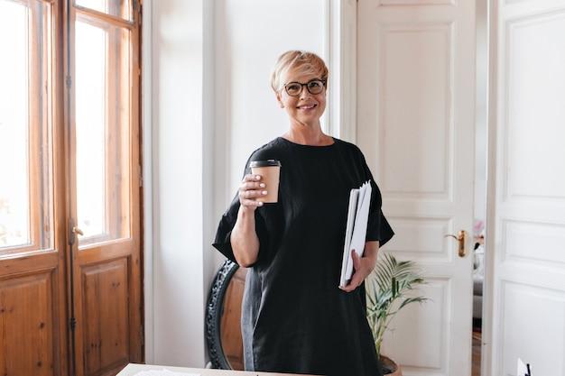 Retrato de uma mulher loira de óculos e vestido preto segurando uma xícara de chá e documentos