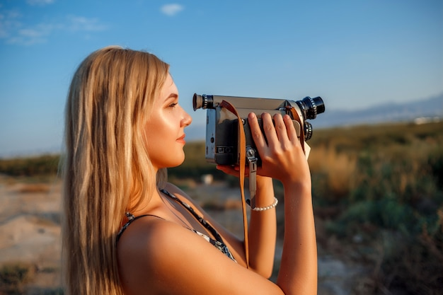 Retrato de uma mulher loira de vestido estampado floral com câmera de vídeo vintage no campo de uva durante o pôr do sol