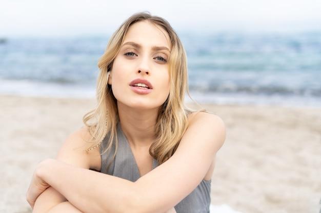 Retrato de uma mulher loira deslumbrante olhando intrigante para a câmera, sentada em uma areia perto do mar