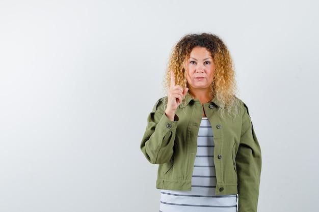 Retrato de uma mulher loira e bonita apontando para cima com uma jaqueta verde e olhando pensativa para a frente