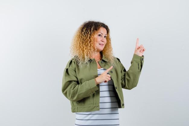 Retrato de uma mulher loira e bonita apontando para o canto superior direito com uma jaqueta verde e uma vista frontal atenciosa