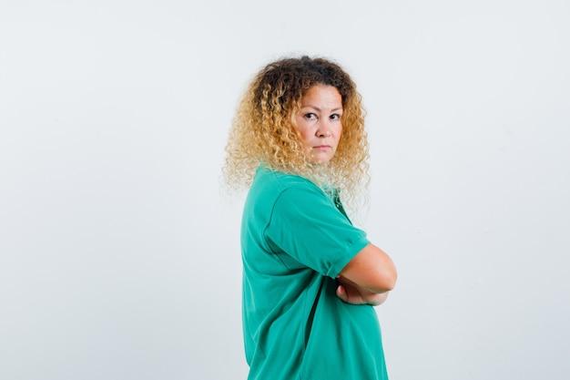 Retrato de uma mulher loira e bonita de braços cruzados em uma camiseta polo verde e com ar sério