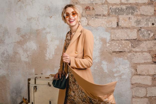 Retrato de uma mulher loira elegante e atraente com casaco bege, caminhando na rua contra uma parede vintage