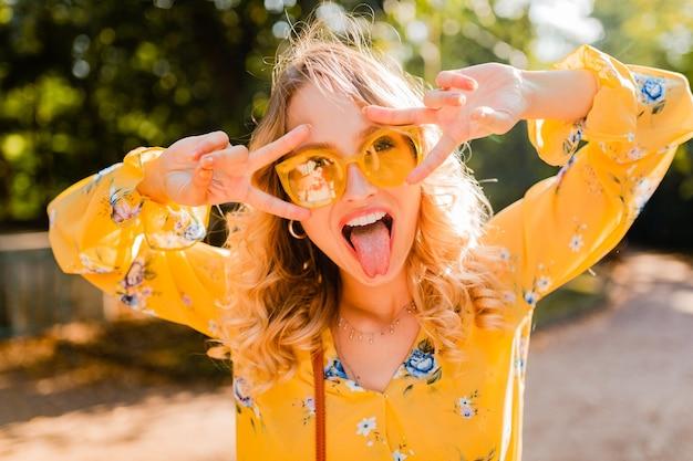 Retrato de uma mulher loira elegante e emocional bonita com blusa amarela usando óculos escuros, expressão engraçada de cara maluca
