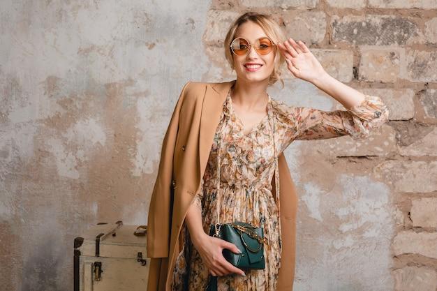 Retrato de uma mulher loira elegante e sorridente atraente com casaco bege, caminhando na rua contra uma parede vintage