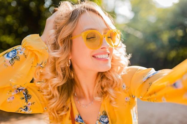 Retrato de uma mulher loira elegante e sorridente bonita em uma blusa amarela usando óculos escuros, fazendo uma foto de selfie