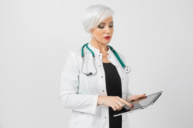 Retrato de uma mulher loira em traje de médicos com tablet nas mãos dela isolado