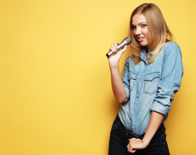 Retrato de uma mulher loira encantadora cantando com microfone sobre o espaço amarelo.