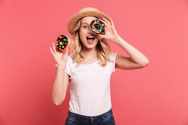 Retrato de uma mulher loira encantadora com chapéu de palha rindo enquanto segura rosquinhas doces saborosas isoladas sobre uma parede rosa
