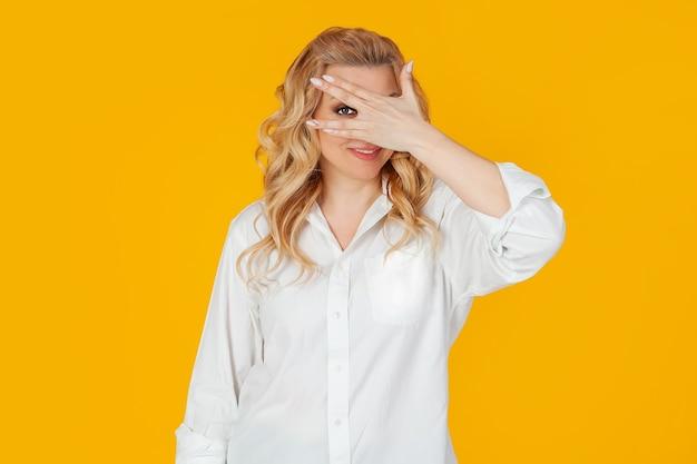 Retrato de uma mulher loira europeia de meia-idade em uma camisa branca, fecha os olhos com as mãos e olha por entre os dedos, sorrindo. de pé sobre um fundo amarelo. um olhar para o futuro.