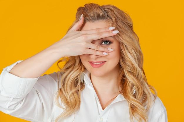 Retrato de uma mulher loira europeia de meia-idade em uma camisa branca, fecha os olhos com as mãos e olha por entre os dedos, sorrindo. de pé sobre um fundo amarelo.