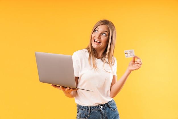 Retrato de uma mulher loira feliz expressando maravilha enquanto segura o computador portátil e o cartão de crédito isolado sobre a parede amarela em estúdio