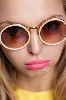 Retrato de uma mulher loira infeliz e frustrada com óculos escuros e camisa amarela sobre fundo azul