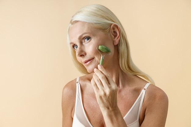 Retrato de uma mulher loira madura com pele brilhante perfeita, olhando para a câmera enquanto usa o tratamento facial de jade