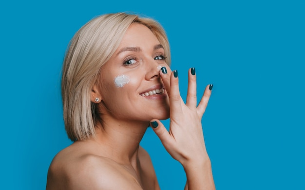 Retrato de uma mulher loira olhando para a câmera enquanto passa creme no nariz