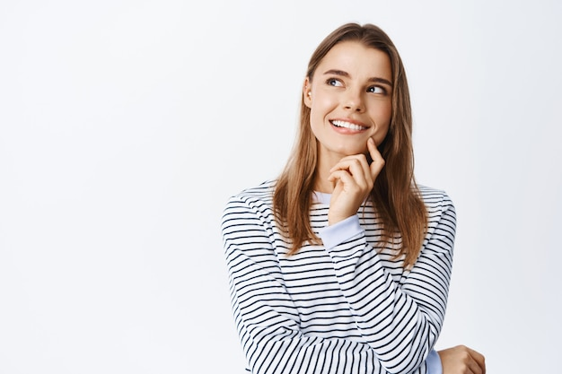 Retrato de uma mulher loira pensativa tendo uma ideia, parecendo pensativa no canto superior esquerdo, imaginando algo bom, encostada em uma parede branca