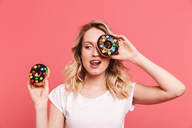 Retrato de uma mulher loira satisfeita vestindo uma camiseta casual sorrindo enquanto segura deliciosos donuts doces isolados sobre uma parede rosa