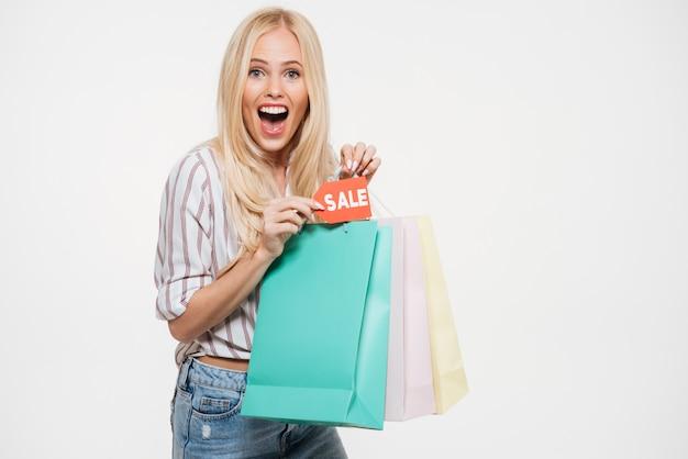 Retrato de uma mulher loira segurando sacola de compras