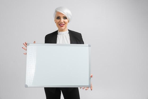 Retrato de uma mulher loira segurando uma placa magnética nas mãos dela isolado na