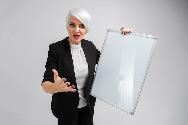 Retrato de uma mulher loira segurando uma placa magnética nas mãos dela isolado no fundo