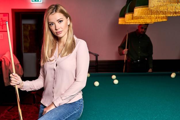 Retrato de uma mulher loira sentada na mesa de bilhar, posando, vestindo roupa casual, no bar, passando um tempo agradável, feriados