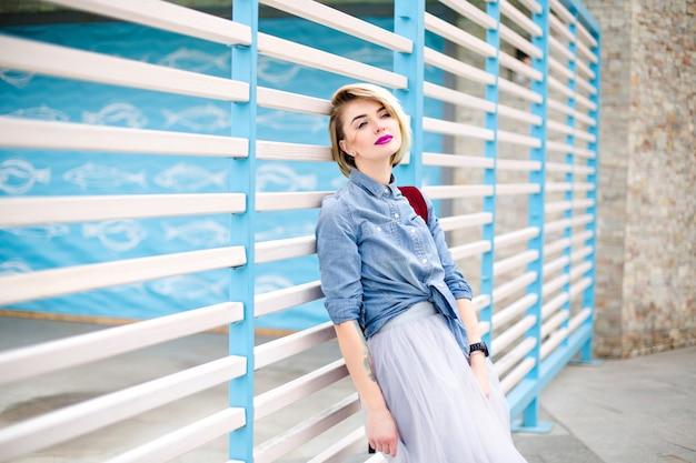 Retrato de uma mulher loira sonhadora com cabelo curto, lábios rosados brilhantes e olhos azuis, vestindo uma camisa jeans azul