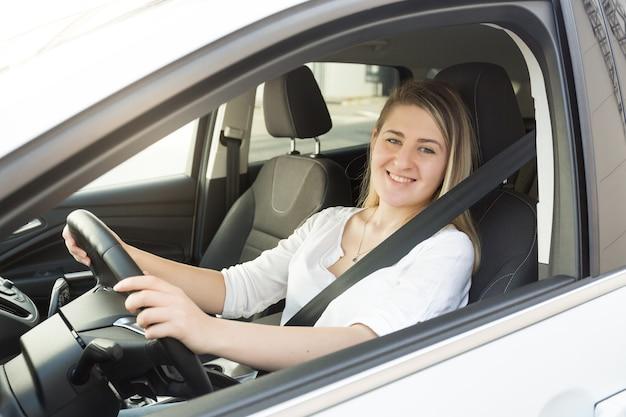 Retrato de uma mulher loira sorridente com camisa branca, dirigindo um carro