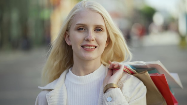 Retrato de uma mulher loira sorridente com sacos coloridos nas mãos no fundo de uma rua pedonal. conceito de loja de compras e roupas. close-up, 4k uhd.