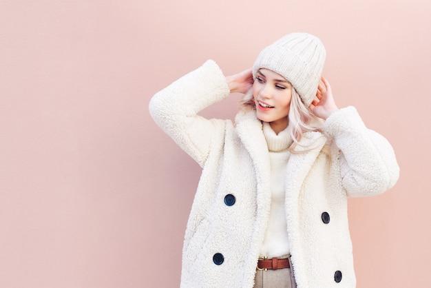Retrato de uma mulher loira sorridente em roupas de inverno, olhando para longe no fundo rosa.