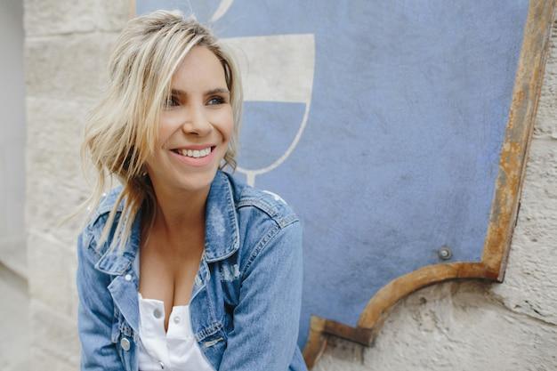Retrato de uma mulher loira sorridente em uma jaqueta jeans