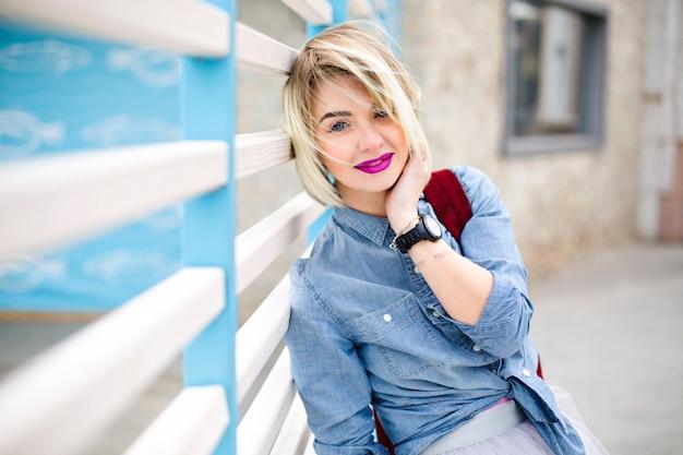 Retrato de uma mulher loira sorridente sonhadora com cabelo curto esvoaçante e lábios cor de rosa brilhantes, vestindo uma camisa jeans azul