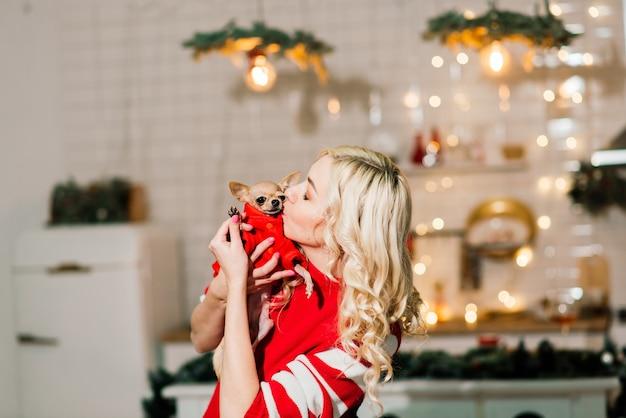 Retrato de uma mulher loira vestindo papai noel de natal segurando cachorros chihuahua em fantasia de natal na cozinha com decoração de natal, sorrindo e olhando para a câmera.