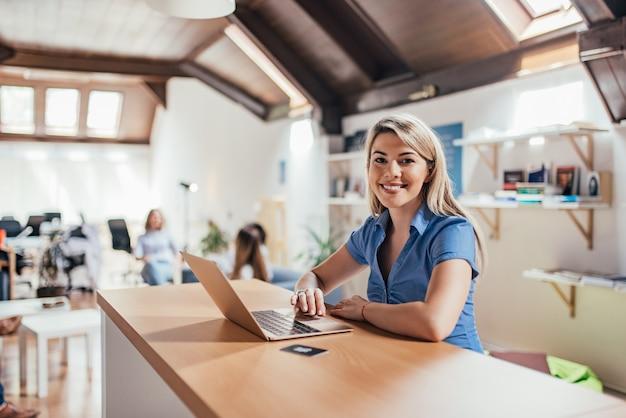 Retrato de uma mulher loura de sorriso que senta-se na frente do laptop no escritório do espaço aberto.