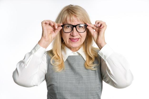 Retrato de uma mulher madura com óculos, sobre um fundo claro. sorria, emoções positivas.