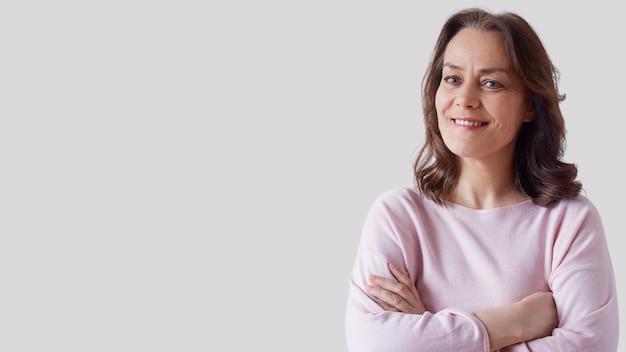 Retrato de uma mulher madura e bonita com um suéter rosa