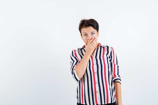 Retrato de uma mulher madura segurando a mão na boca com uma camisa listrada e olhando para a frente Foto gratuita